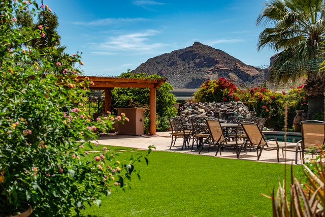 Big backyard with green grass and a lot of outdoor furniture. The mountains are in the background.